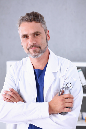 Handsome mature smiling male doctor with arms crossed on chest Stock Photo