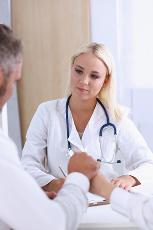 Young couple hold arms together in family doctor office Stock Photo