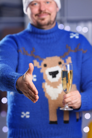 handclasp: Man wearing warm blue deer sweater hold in arm Stock Photo