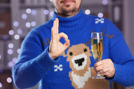 Man wearing warm blue deer sweater hold in arm champagne