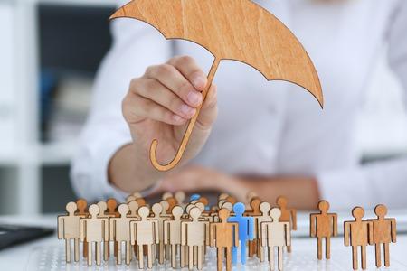 insurer: The female hand holds a miniature umbrella
