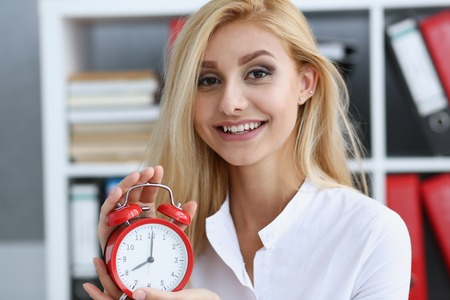 Smiling business woman holding in hand clock