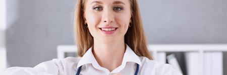 Beautiful smiling doctor hold in arms red heart Stock Photo