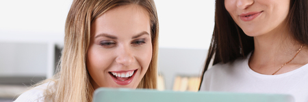 Two pretty women watching a funny video