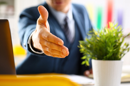 Man in suit and tie give hand as hello in office Stockfoto