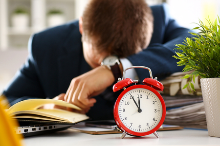 Red alarm clock shows late time closeup Stock Photo