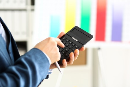 Male arm in suit hold calculator pressing buttons Archivio Fotografico