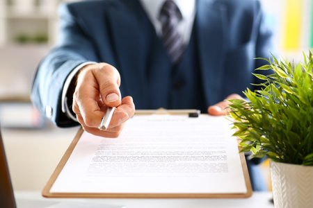 Male arm in suit offer contract form on clipboard