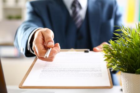 Mannelijke arm in pak aanbod contractvorm op klembord Stockfoto - 89722067