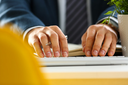 Male arms in suit typing on silver keyboard