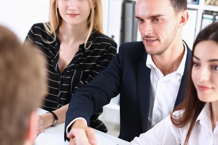 Smiling man in suit shake hands as hello Standard-Bild