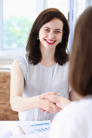 Business woman and woman shake hands as Stock Photo