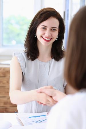Zakelijke vrouw en vrouw schudden elkaar de hand als