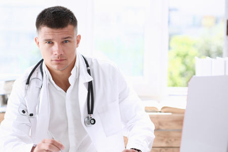 Handsome smiling male doctor sit at Stock Photo