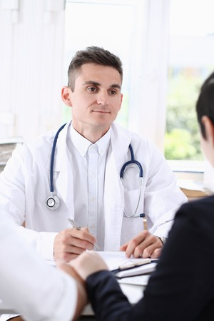 Male family doctor listen carefully young