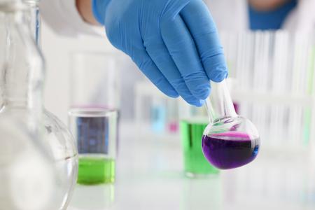 Een mannelijke chemicus houdt reageerbuis glas Stockfoto - 89852351