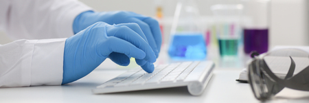 Employee chemical laboratory teacher chemist knocks his fingers keyboard makes notes electronic journal records the analysis data from reactions examining test tubes with the substance arm in gloves. Stock Photo