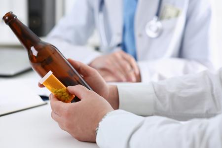 Alcoholic hold in hand empty bottle Standard-Bild