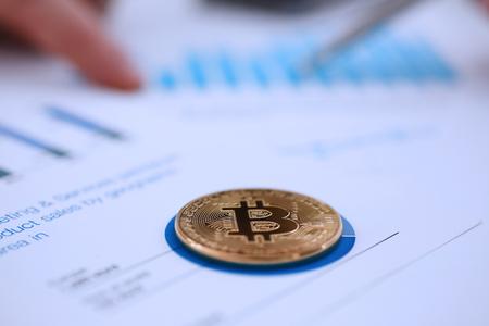 Golden btc sign coin lying at stats graph closeup Stock Photo