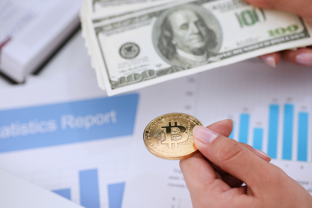Hands with a coin bitcoin and fan of dollars