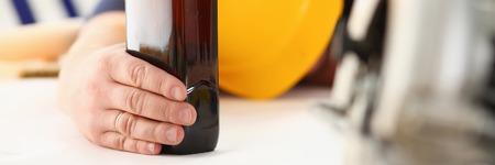 Arm of drunken worker in yellow helmet
