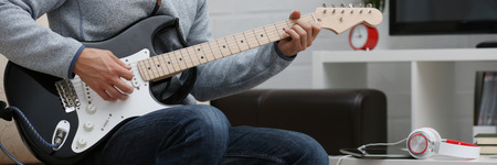 Male hands tuning guitar