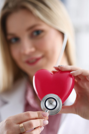 Beautiful smiling blond female doctor hold Stock Photo