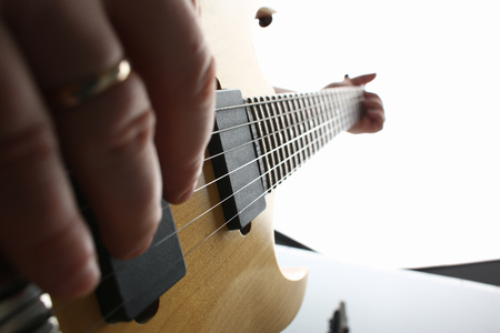Male hands playing electric guitar on maple fretboard Stock Photo