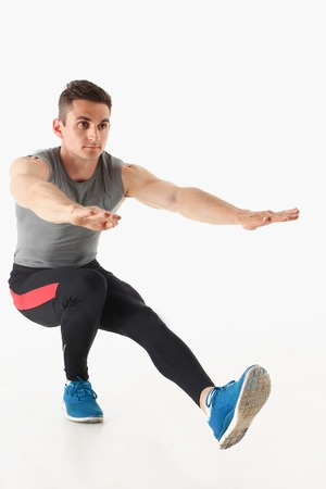 Fitness man crouchs from floor demonstrates