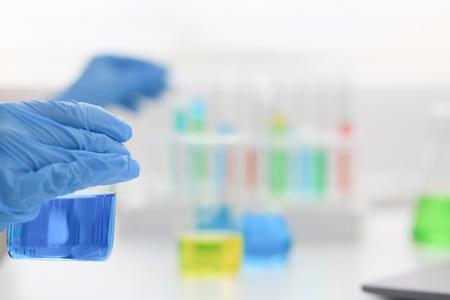 Female chemist holds test tube of glass