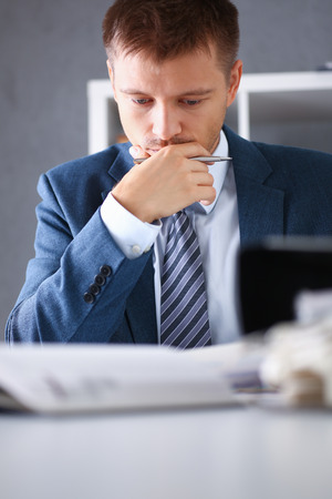 Serious businessman in the office examines Stock Photo