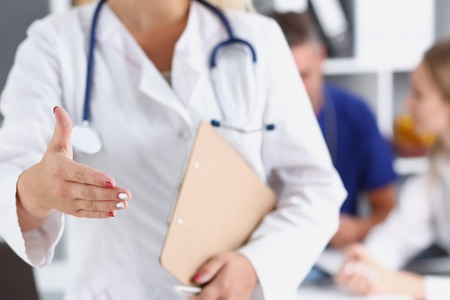 Female medicine doctor hold pad and give arm Banque d'images
