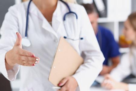 Female medicine doctor hold pad and give arm Archivio Fotografico