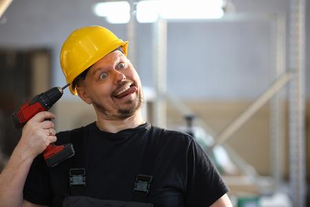 Idiot worker using electric drill portrait Фото со стока