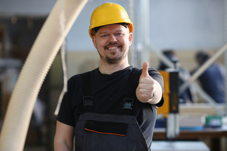 Smiling worker in yellow helmet show confirm sign Фото со стока