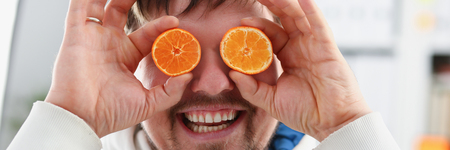 Male hands hold a cut fruit at eye level