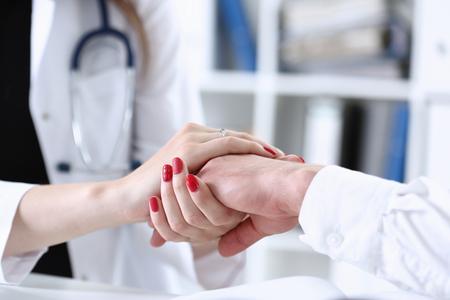 Friendly female doctor hold male patient hand Foto de archivo