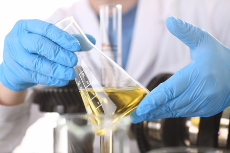 Male hands in protective gloves hold test tube