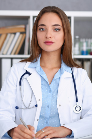Female doctor hold hold in arm silver pen Stock Photo