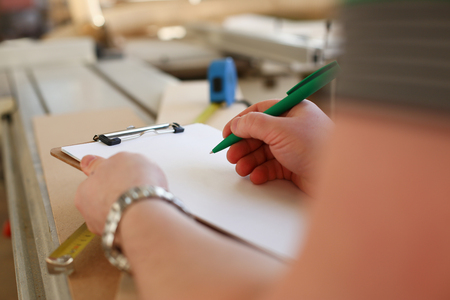 Arms of worker making notes on clipboard with green pen Stock Photo