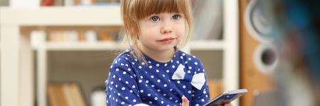 Cute little girl on floor carpet use cellphone