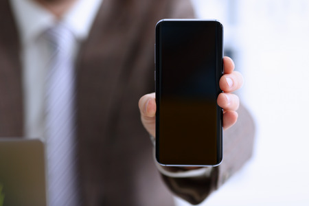 Male arm in suit show in camera phone display