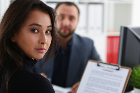 young beautiful woman sit on chair at table in office in cabinet of her boss hold binder in arms 免版税图像