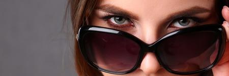 Beautiful young smiling brunette girl wearing sunglasses
