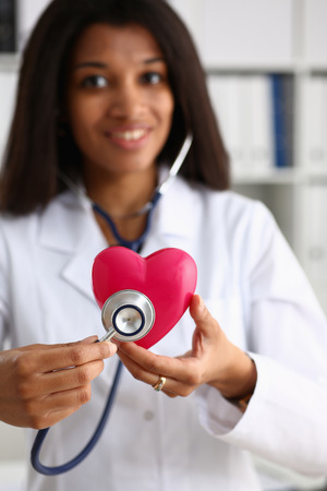 A beautiful black smiling female doctor holding a red heart Standard-Bild