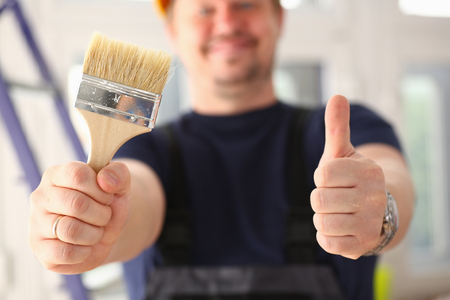 Arms of worker hold paint brush and show confirm