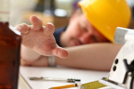 Arm of drunken worker in yellow helmet hold liquor