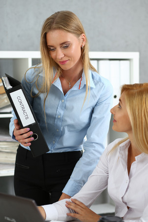 Female employee show pack of documents to busy clerk