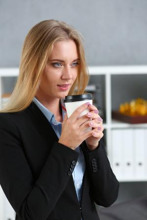 Femme d'affaires souriante, boire du café dans une tasse en papier Banque d'images