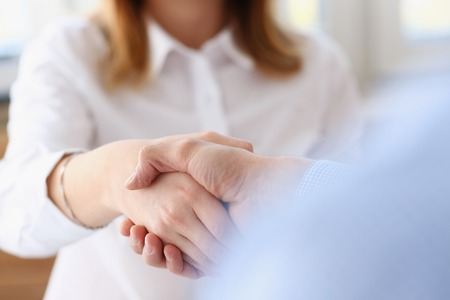 Businessman and woman shake hands after meeting Stock Photo